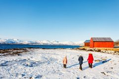Mother and kids outdoors on winter. Beautiful family of mother and kids enjoying snowy winter day outdoors at beach surrounded by fjords in Northern Norway Stock Images