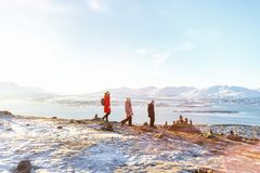 Mother and kids outdoors on winter. Beautiful family of mother and kids have a pleasant time on snowy winter day outdoors enjoying views near Tromso Norway Royalty Free Stock Photo