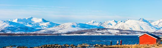 Mother and kids outdoors on winter. Panorama of beautiful family of mother and kids enjoying snowy winter day outdoors at beach surrounded by fjords in Northern royalty free stock photos