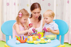 Mother with kids paint Easter eggs. Beautiful young mother with two sweet kids decorated traditional Easter eggs with colorful paint, happy family concept royalty free stock photos