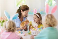 Mother and kids, family coloring Easter eggs. Mother and kids with pet rabbit color Easter eggs. Mom, little girl and boy with bunny ears dying and painting for royalty free stock photos
