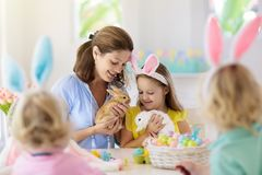 Mother and kids, family coloring Easter eggs. Mother and kids with pet rabbit color Easter eggs. Mom, little girl and boy with bunny ears dying and painting for stock image