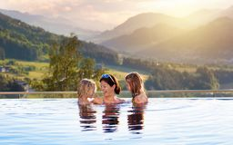 Family in swimming pool with mountain view. Mother and kids play in outdoor infinity swimming pool of luxury spa alpine resort in Alps mountains, Austria. Spring royalty free stock image