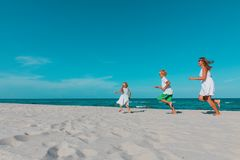 Mother with kids play run on tropical beach royalty free stock images