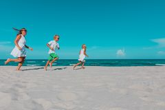 Mother with kids play run on tropical beach. Family vacation stock images