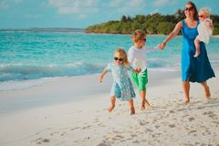 Mother with kids play run on tropical beach. Vacation stock images
