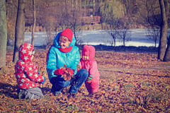 Mother with kids playing in autumn Stock Images