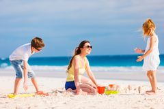 Mother and kids playing at beach. Mother and kids making sand castle at tropical beach royalty free stock photography