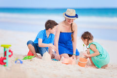 Mother and kids playing at beach Stock Photos