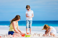 Mother and kids playing at beach Stock Image
