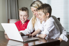 Mother with kids playing on laptop computer Stock Photos