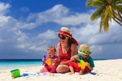 Mother and kids playing on sand beach. Mother and kids playing on tropical sand beach Stock Photo