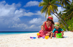 Mother and kids playing on tropical beach Stock Photo