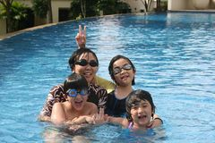Mother and kids in the pool. Mother and kids playing happily in the pool Stock Photos