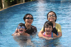 Mother and kids in the pool. Mother and kids playing happily in the pool Stock Photo