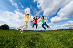 Mother with kids running. Active family - mother with kids running on green meadow Royalty Free Stock Photos