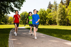 Mother with kids running in park. Active family - mother with kids jumping, running in city park Royalty Free Stock Photo