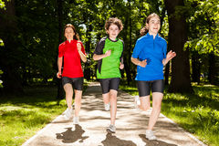 Mother with kids running in park. Active family - mother with kids jumping, running in city park royalty free stock images