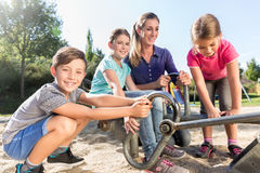 Mother and kids in sandbox playing with digger Stock Image
