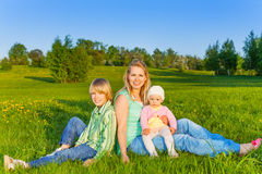Mother with kids sits on grass in park Royalty Free Stock Photos