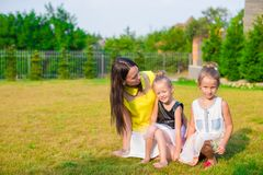 Mother and kids sitting outdoors at beautiful Royalty Free Stock Photos