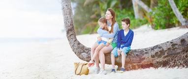Mother and kids sitting on palm Royalty Free Stock Image