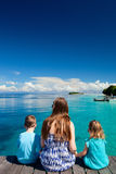 Mother and kids sitting on wooden dock Stock Image