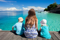 Mother and kids sitting on wooden dock Stock Photo