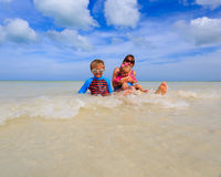 Mother with kids splasing water at the sea Stock Photos