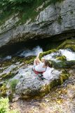 Mother with kids taking a selfie, sitting on a rock by a mountain stream on a family trip. Outdoor lifestyle, natural parenting, childhood experience concept stock image