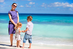 Mother with kids on tropical beach Stock Images