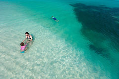 Mother and kids at tropical beach. Above view of mother and kids enjoying tropical beach vacation Stock Photography