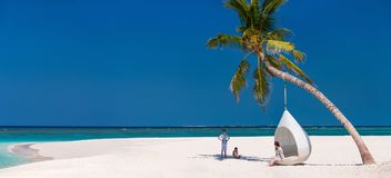Mother and kids at tropical beach. Panorama of family mother and kids enjoying tropical beach vacation Royalty Free Stock Images