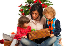 Mother with kids under Christmas tree Royalty Free Stock Images
