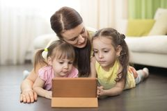 Mother with kids use ipad lying on floor in living room. Mother with children use ipad lying on floor in living room Stock Photos
