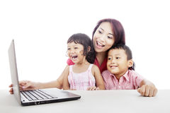 Mother and kids using computer. Happy young mother with her children using ultrabook laptop computer Royalty Free Stock Photo