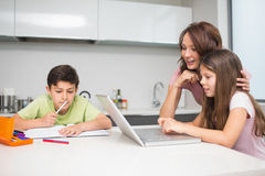 Mother with kids using laptop in kitchen Royalty Free Stock Photography