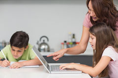 Mother with kids using laptop in kitchen Royalty Free Stock Image