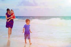 Mother with kids walking on sand beach Royalty Free Stock Images