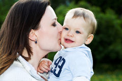 Mother kiss baby boy. In park Stock Photography