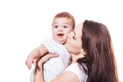 Mother kiss her baby isolated. Young beauty mother kissing her baby on the white background Stock Photography