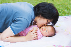 Mother kiss her baby at park Stock Photo
