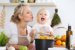 Mother kiss her child daughter while cooking pasta for the breakfast. Concept of happy family in the kitchen Royalty Free Stock Photo
