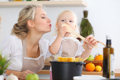 Mother kiss her child daughter while cooking pasta for the breakfast. Concept of happy family in the kitchen.  Stock Photography