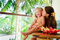 Mother kiss her daughter at tropical garden Stock Photos