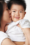 Mother kiss her son Stock Images