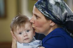 A mother kisses a child. Belarus, the city of Gomel, St. Nicholas Monastery.June 11, 2016.Baptism of the Child.A mother kisses a baby.Mother pities her son Royalty Free Stock Photography