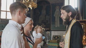 The mother kisses a cross during the ritual of baptizing of her son in church stock video footage