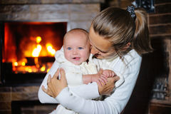 Mother kisses daughter at the burning fireplace Stock Images