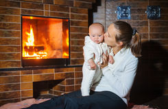 Mother kisses daughter at the fireplace Stock Photo